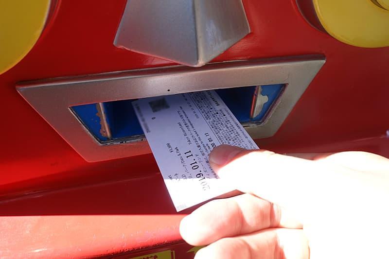 発券機にチケットの2次元バーコードをかざす